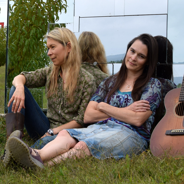 The Neilds sisters sitting outside on grass